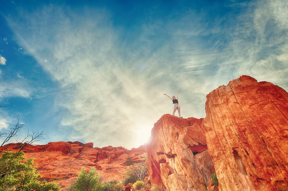 woman standing atop a canyon with her arms to the sky