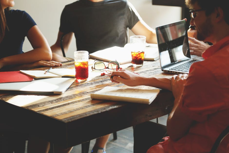 employees sitting around a table collaborating company culture